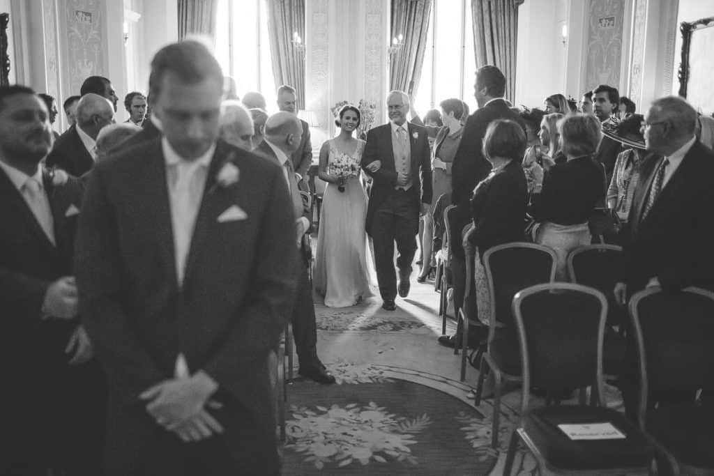 Bride arriving down the aisle at Lansdowne Club with groom looking nervous